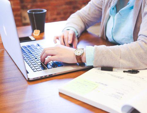 Persona treballant amb l'ordinador portàtil, amb llibre i tassa de te