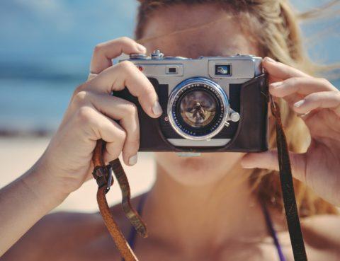 Persona subjectant càmera de fotos sobre la seva cara