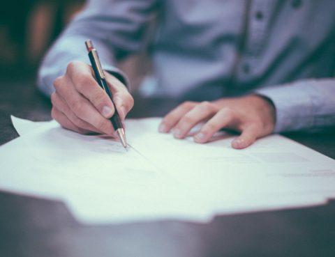 Persona escrivint en un document sobre una taula