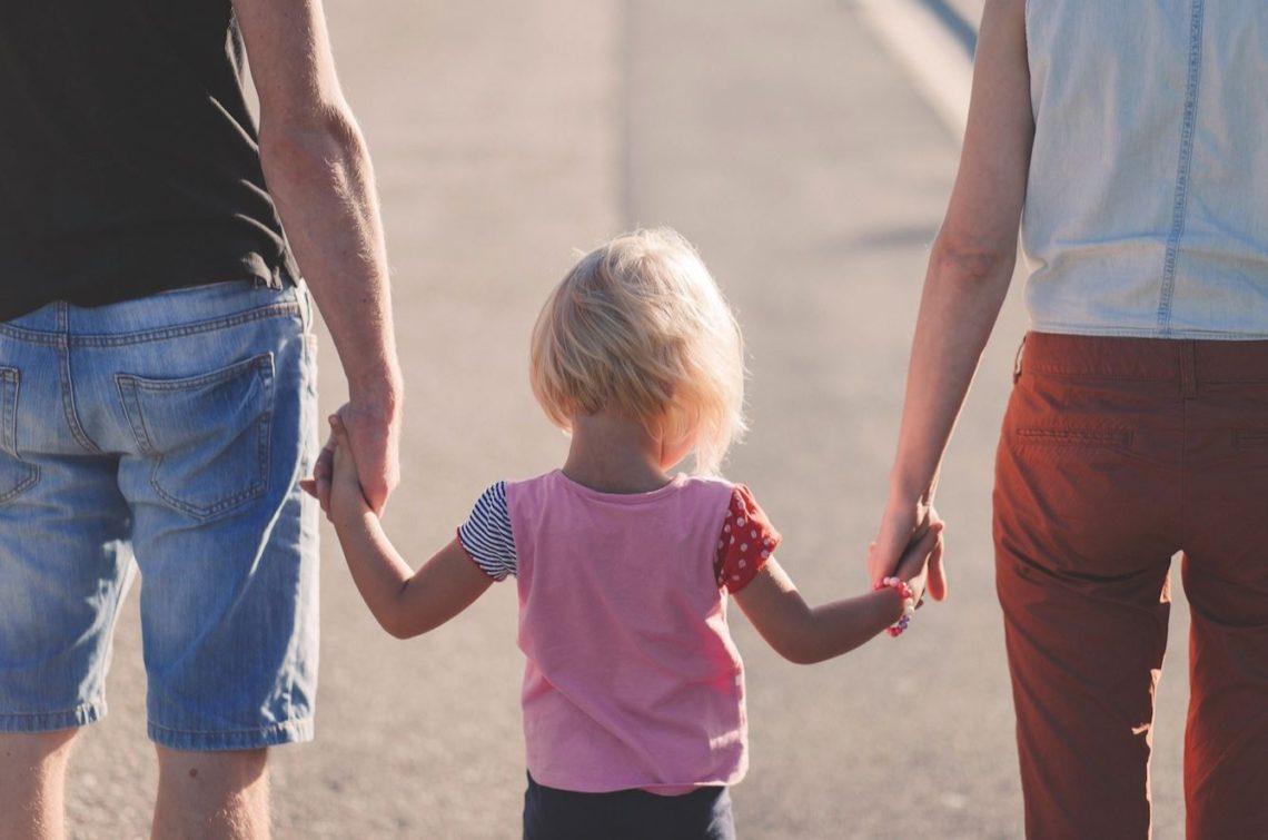 Infant agafant la mà dels seus pares