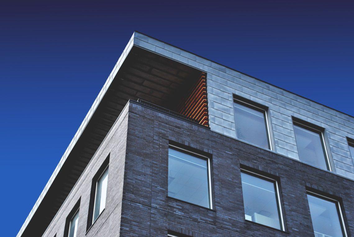 Finestres de la cantonada d'un edifici i cel blau de fons