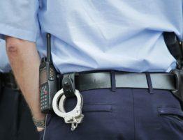 Policia d'esquenes, amb les esposes penjades
