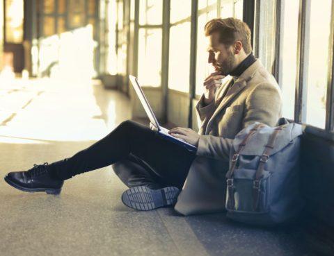 Hombre trabajando en el suelo en un viaje (dietas)